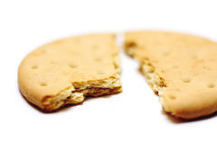 Broken biscuit. A biscuit, broken in half, on a white background Royalty Free Stock Photo