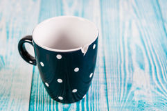 Broken black ceramic cup, blue wooden background, free space Stock Photo
