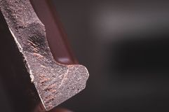 Broken black chocolate closeup with texture and blurred background stock image