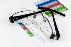 Broken black glasses on business graph Stock Images