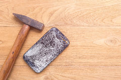 Broken of black smartphone and hammer on wooden table background royalty free stock image