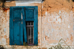 Broken blue window with orange wall of old building. Royalty Free Stock Photo