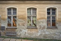 Broken and boarded-up windows in an old abandoned house Stock Photos