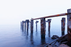 Broken Boat Dock. Photograph of a broken worn down boat dock, in the morning mist. Shore is cluttered with trash Royalty Free Stock Photo