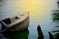 Broken boat sinking in a lake stock photography