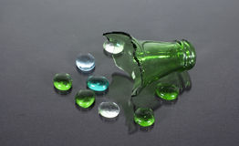 Broken bottle. A broken bottle top and glass beads on a black background Royalty Free Stock Photo