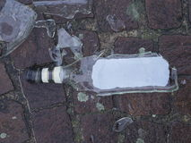 Broken bottle on the ground. Puzzle of a broken bottle of schnaps resting on the ground Free themselves from alcohol addiction Stock Image