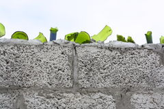 Broken Bottle Security Wall. Broken glass imbedded at the top of a block wall stock photo