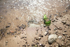 Broken bottle of sharp edged lying on the riverbank Royalty Free Stock Photography