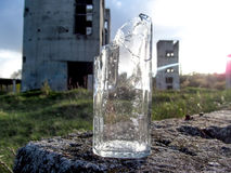 A broken bottle stands on a vacant lot in front of two destroyed towers. In the cracks of the glass play the rays of the sun Royalty Free Stock Image