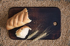 Broken bread and ears on a kitchen board against a background of wheat grains. Broken bread and ears on a kitchen board against the background of wheat grains royalty free stock photography