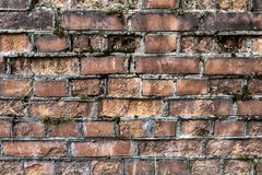Broken brick wall background in sunny summer day. Abstract red brick old wall texture background. Ruins uneven crumbling red brick royalty free stock photography