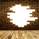 Broken brick wall in the room. Broken hole in the brick wall of room with wooden floor Stock Image