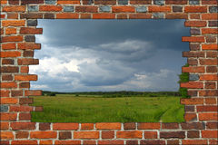 Broken brick wall and view to field with thunder Stock Photos