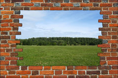 Broken brick wall and view to the summer field Royalty Free Stock Image