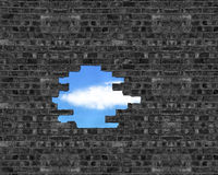 Broken bricks wall with a hole and cloud, blue sky outside Stock Photos