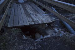 Broken bridge from a spring flood of a usually small river in a forest in northern Sweden. stock photo