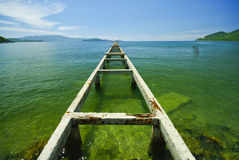 Broken bridge to the emerald sea Stock Photography