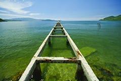 Broken bridge to the emerald sea Stock Photography