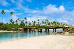 Broken bridge under palm trees between islets over lagoon, North Tarawa atoll, Kiribati, Micronesia, Gilbert islands, Oceania, stock photo