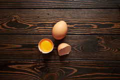 Broken brown eggs. Broken brown egg  on wood background Stock Photos