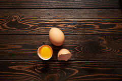 Broken brown eggs. Broken brown egg  on wood background Stock Images
