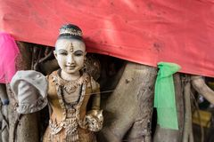 Broken Buddha statue and old religious dolls under tree in Thail. And Stock Photos