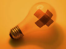 Broken bulb. A roken light bulb with 2 bandaids on it. Orange hues Stock Photography
