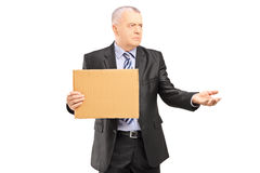 Broken businessman holding a piece of cardboard and begging Royalty Free Stock Photos