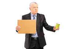 Broken businessman holding a piece of cardboard and cup Royalty Free Stock Photography