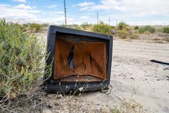 A broken, busted old CRT TV set sits abandoned and rotting in the desert of California.  royalty free stock image