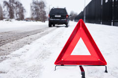 Broken Car. Parked with a warning triangle in a snowy street Stock Photo