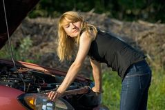 Broken car. Young woman and car with opened hood Royalty Free Stock Image