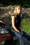 Broken car. Young woman and car with opened hood Royalty Free Stock Photos
