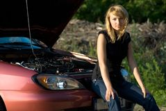 Broken car. Young woman and car with opened hood Stock Image