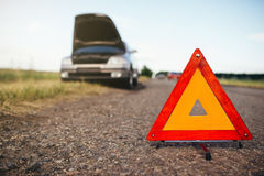 Broken car concept, breakdown triangle on road. Broken car concept, breakdown triangle on asphalt road. Problem with vehicle, warning sign Royalty Free Stock Photos