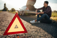 Broken car concept, breakdown triangle on road. Broken car concept, breakdown triangle on asphalt road. Problem with vehicle, warning sign Stock Photos