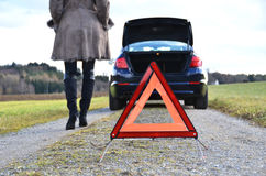 Broken car, girl and triangle Royalty Free Stock Photo