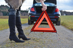 Broken car, girl and triangle Stock Photos