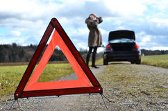 Broken car, girl and warning triangle Stock Photography