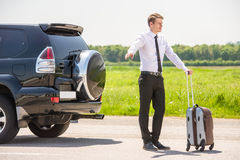 Broken car. Handsome businessman standing on a highway and catching a car Royalty Free Stock Images