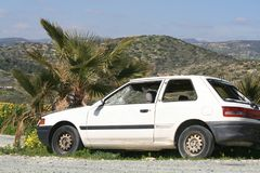 Broken car by the mountain road. White car with broken windows standing by the mountain road close to a palm tree on a spring sunny day royalty free stock images