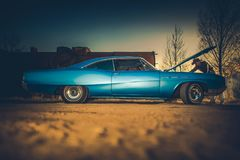 Broken Car Problem. Caucasian Men Wester Wear Trying To Fix His Classic Ride in the Remote Countryside Place Royalty Free Stock Photo