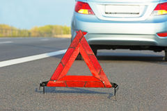 Broken car with red triangle sign. Royalty Free Stock Images