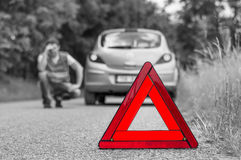 Broken car on the road and unhappy driver with red triangle. Broken car on the road and unhappy driver with red warning triangle - black and white concept royalty free stock images