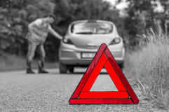 Broken car on the road and unhappy driver with red triangle. Broken car on the road and unhappy driver with red warning triangle - black and white concept stock images