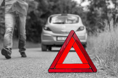 Broken car on the road and unhappy driver with red triangle. Broken car on the road and unhappy driver with red warning triangle - black and white concept stock photo