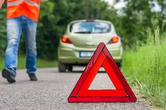 Broken car on the road and unhappy driver. With red warning triangle royalty free stock images
