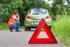 Broken car on the road and unhappy driver. With red warning triangle royalty free stock image