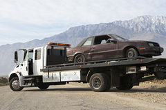 Broken Car On Tow Truck. Damaged car being transported on tow truck with mountain range in the background Stock Photos